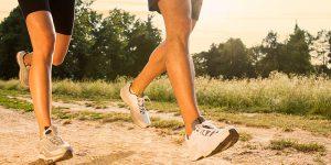 Leg View of Athletes Running on Grassy Road