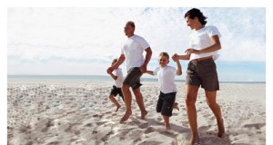 Family of Four Holding Hands at Beach