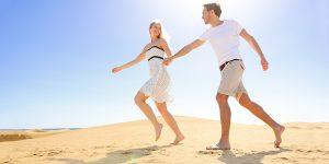 Couple Running Barefoot on Sandy Beach