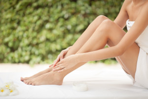 Female's Arms over Bent Knees Sitting on Spa Bed
