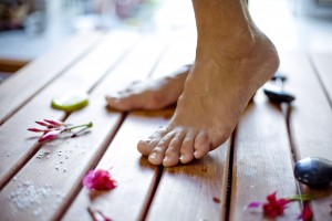 Bare Feet on Wooden Floor Next to Rocks and Flowers Copy