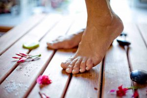 Bare Feet on Wooden Floor Next to Rocks and Flowers