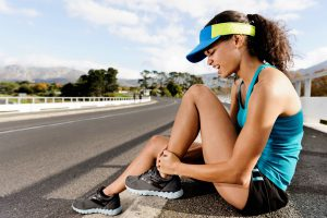 Female Runner Sitting on Ground Holding Ankle in Pain Copy
