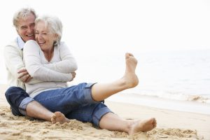 Old Couple Embracing On Beach With Bare Feet in Sand
