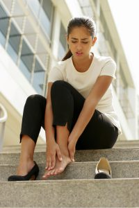 Business Woman With High Heels Holding Foot in Pain
