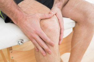 Man's Hands Holding Knee Sitting on Massage Table