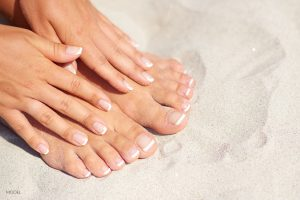 Manicured Hands and Feet on Beach Sand