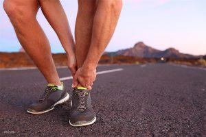 Male Runner Holding Ankle in Pain on Desert Road