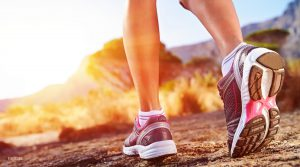 Close Up of Female Model's Running Shoes on Rock