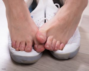 Bare Feet Touching Resting on Top of Sneakers Copy