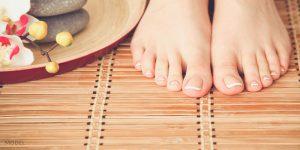 Manicured Female Feet on Bamboo Floor