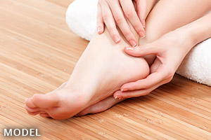 Woman with bare feet touching her ankle