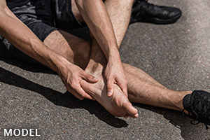 Male sitting on the road with a sports injury