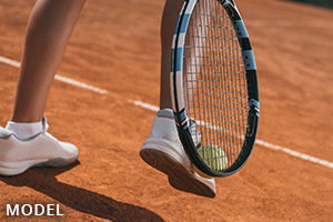 Feet of a person playing tennis wearing sports shoes.